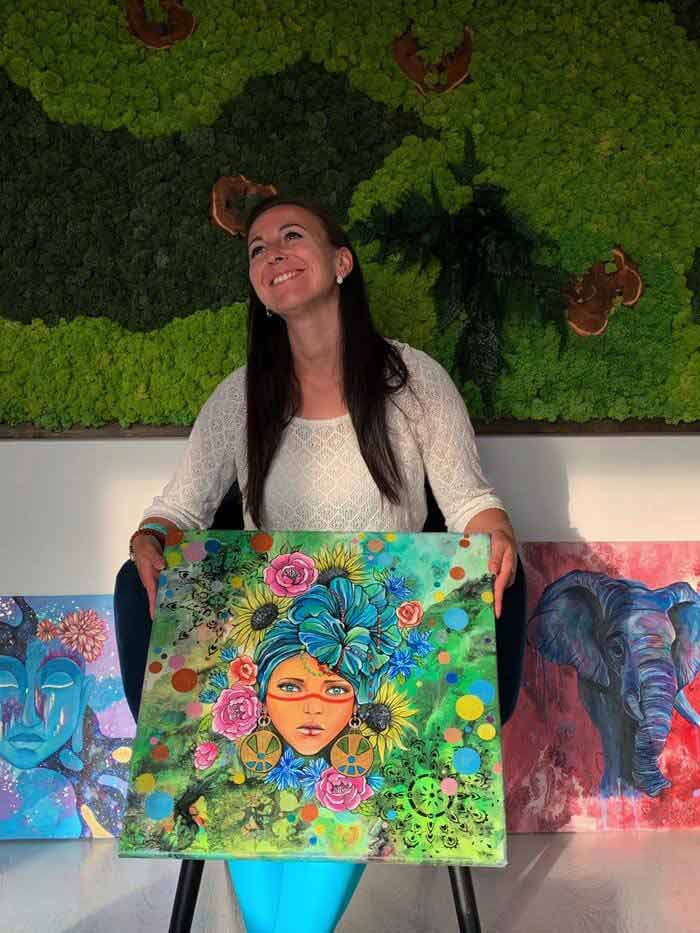 Marianna with colorful artwork by Marianna